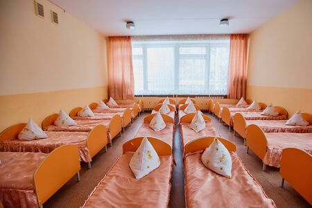 Beds and cots in brightly colored dormitory of a nursery.A lot of childrens cots.