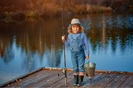 Little girl fisherman with a fishing rod and a bucket of fish on a wooden pier