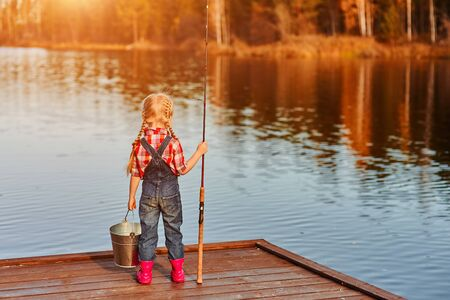 little girl with a fishing rod and a bucket came fishing and looks at the pond. Back view.