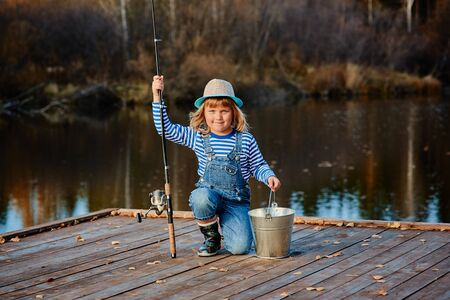 Little girl fisherman with a fishing rod and a bucket of fish on a wooden pier.