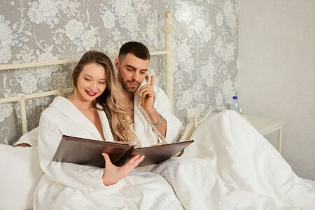 Young couple lying in bed calls room service to order food from hotel restaurant. Stock Photo
