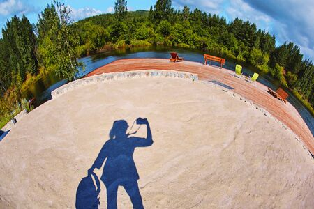 the sandy surface of the beach play area is formed by bright daylight, which falls under the shadow of the silhouette of the photographer who photographed himself on the fisheye lens