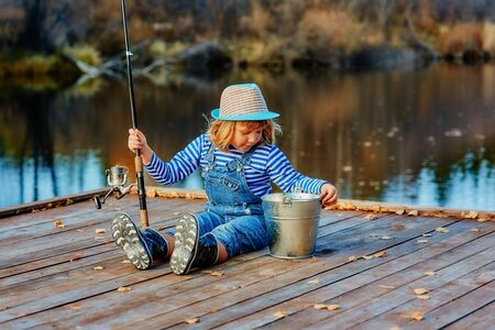 A little girl with a fishing rod looks at the catch of fish in a bucket. Stok Fotoğraf