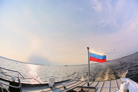 Russian flag waving in the wind on the background of water and sky.