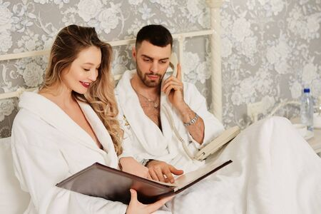 Newlyweds in hotel white coats woke up, look at the menu and make a phone order for Breakfast delivered to the room. Imagens