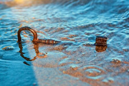 An old lost key in the sand is a newfound opportunity. The concept of success, luck and unexpected wealth 版權商用圖片
