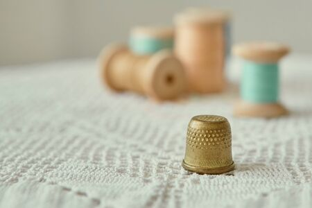Vintage brass thimble close-up.  It is on an old handmade knitted tablecloth.  In the background vintage wooden bobbins with sewing threads.