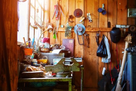 Workshop or garage on a farm in an old wooden barn. A lot of different tools lying around in a mess to repair any equipment.