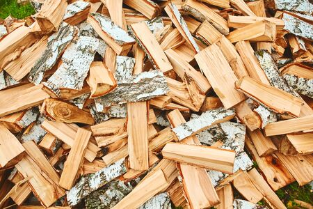 Background of a stack of split logs in a woodpile for use as domestic heating in winter with a close up view of the cross-section at the ends. 스톡 콘텐츠