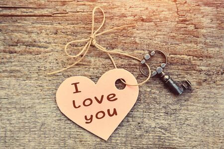 Holiday card with the words I love you. The heart with the antique key lies together on a wooden Board. Valentine. The view from the top. Stok Fotoğraf