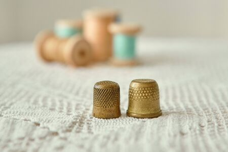 Two vintage thimbles close-up, in the background old wooden bobbins with sewing threads.  Are on the tablecloth antique hand knit lace