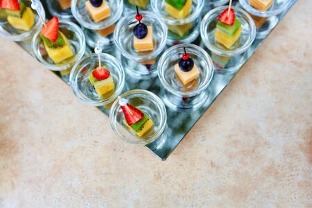 Assorted canapes of fruit and cheese on a glass platter on the background of glasses and champagne. Catering. Imagens