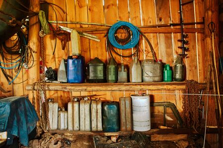 A group of old canisters and cylinders stand on shelves in a wooden shed Imagens