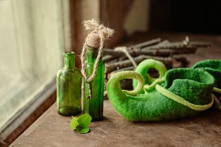 Colorful felted green shoes stand next to antique glass bottles, a leaf of clover and a bundle of firewood. Imagens