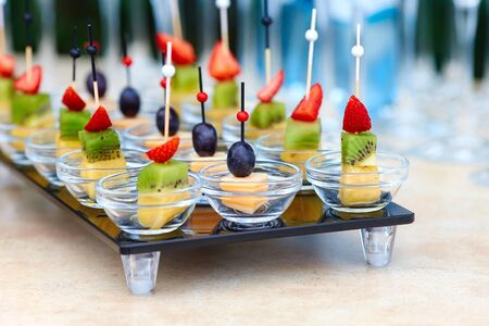 Assorted canapes of fruit and cheese on a glass platter on the background of glasses and champagne. Catering. Stock Photo