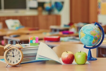 Empty classroom with learning objects, alarm clock and globe. The concept of a break in the lesson. Place for text. Imagens