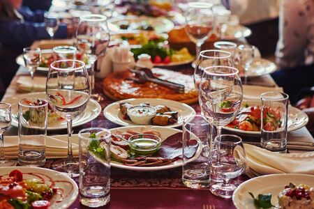 A group of people at a long table with food. The concept for the joint celebration of memorable dates or holidays. Imagens