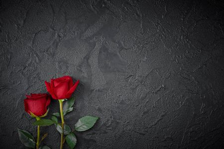 Red roses are placed on a black textured background. A sign of condolence, sympathy loss. Space for your text.