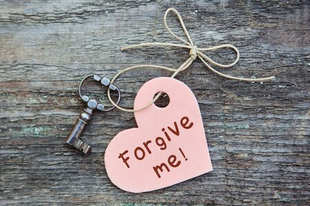 An apology card with the words forgive Me. A heart with an antique key lies together on a wooden Board. The concept of reconciliation. The view from the top. Imagens
