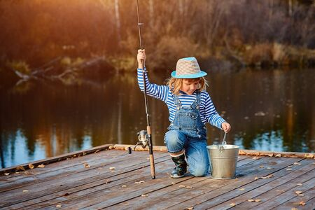 A little girl with a fishing rod looks at the catch of fish in a bucket. Imagens