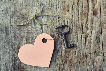 Handmade heart with antique key together lying on wooden Board. Valentine. Space for text. The view from the top.