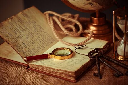 Old vintage items of the treasure hunter, traveler and discoverer - a magnifying glass, old manuscripts, a globe, keys to chests. The concept of luck, unexpected wealth, luck