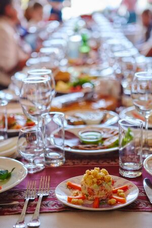 A group of people at a long table with food. The concept for the joint celebration of memorable dates or holidays.