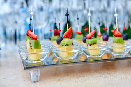Fruit canapes on a glass tray, on the background of wine glasses and champagne. Catering concept.