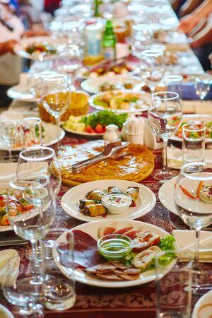 Mesa de banquete larga. Bebidas y snacks en la mesa. La gente está sentada a la mesa. Concepto de celebraciones conjuntas. Foto de archivo