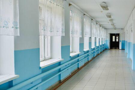 a public school, a long empty corridor with blue walls