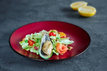 Seafood salad with citrus in a round plate on a grey textured background.