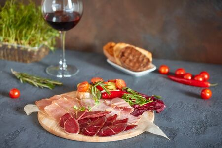 Assorted meat delicacies, cut into thin slices on a round wooden Board. Decorated with bruschetta with vegetables and fresh herbs.
