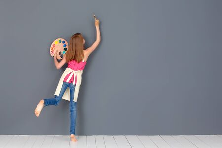 Cute little girl painting on wall in empty room.