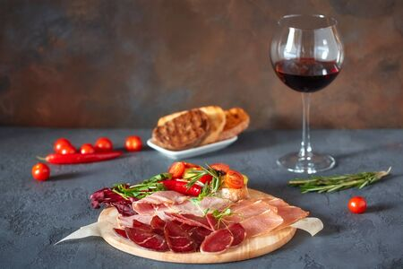 Assorted meat delicacies, cut into thin slices on a round wooden Board. Decorated with bruschetta with vegetables and fresh herbs. Imagens