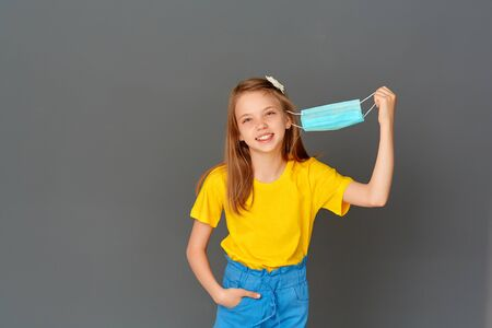 Happy smiling little girl stands holding a mask in her hand on a gray background, she likes to breathe without a mask, the coronavirus is over, the end of staying at home