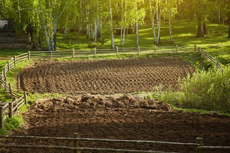 Plowed field prepared for planting. Vegetable garden in the village for potatoes, beets and other home vegetables. Spring is a sunny day