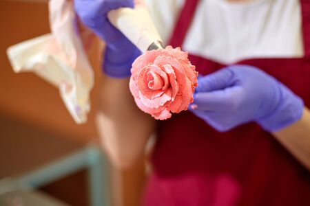 The pastry chef makes a rose flower out of buttercream to decorate the cake. The cream is squeezed out of the pastry bag through a special nozzle