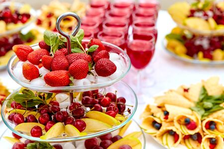 Close-up plate with berries, strawberries. raspberries, cherries, blueberries, and baked goods. Buffet table at the festival. Catering concept.
