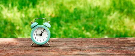 Web banner of the concept of time saving, alarm clock on the background of a Sunny meadow.