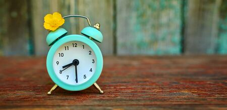 The concept of daylight saving time and saving time. Turquoise alarm clock on a wooden texture background, web banner with space to copy.