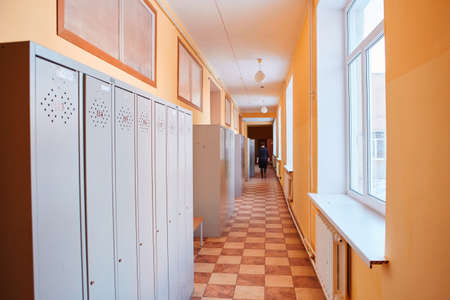 Gray metal outdated lockers in the empty school corridor of the old school.