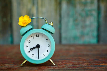 The concept of daylight saving time and saving time. Turquoise alarm clock on a wooden texture background
