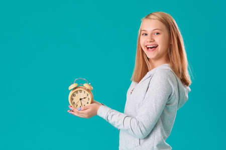 A teenage girl holds an alarm clock, standing on an isolated turquoise background, very happy and excited, the expression of a winner, she celebrates the victory by shouting with a big smile.