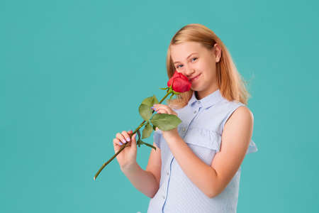 Portrait of a happy girl on a turquoise background. Holding a red rose in his hands and enjoying its fragrance.
