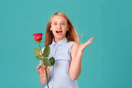 Surprised girl holding a red rose in her hands, she is delighted with the gift. 版權商用圖片