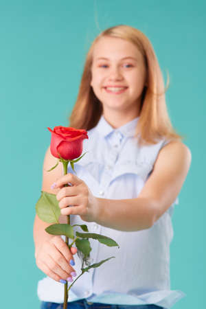 Cute smiling girl gives a red rose as a gift. Selective focus. 版權商用圖片