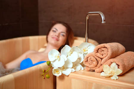 A woman who has Spa treatment and recreation in a wooden hot tub made of cedar.