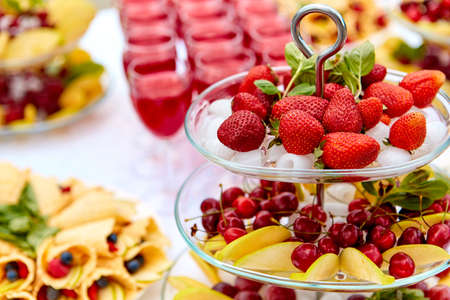 Close-up plate with berries, strawberries. raspberries, cherries, blueberries, and baked goods. Buffet table at the festival. Catering concept