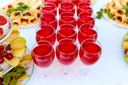 A row of glasses with red drinks, juice, champagne or wine at a party. Catering. Glassware on the table with a white tablecloth. Festive buffet for the holiday