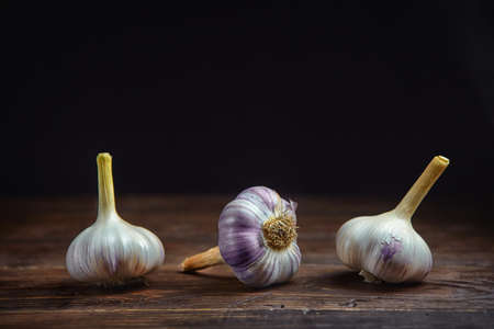 Horizontal view of three garlic heads on a black wooden background 版權商用圖片